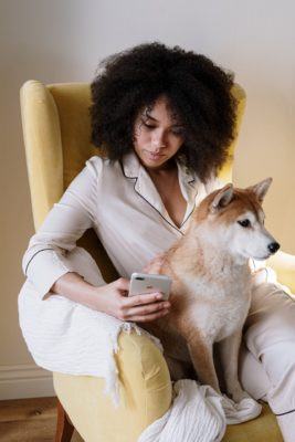 Woman sitting in yellow chair with her hairy pet dog